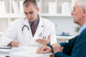 Portrait of handsome male doctor talking with senior patient