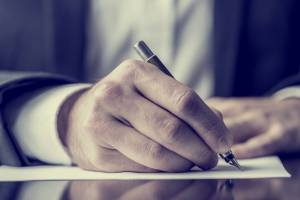 Closeup of man's hand signing a document