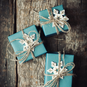 Three Festive Boxes in Blue Paper Decorated with Snowflakes and Linen Cord on Wooden Table.