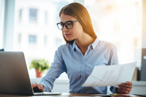 Young woman in glasses using laptop and holding documents while sitting at her working place