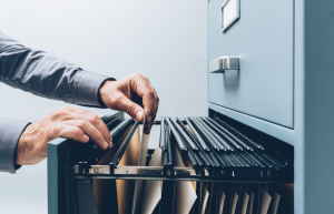 Office clerk searching for files in a filing cabinet