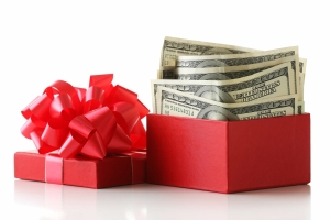 Bundle of one hundred dollar bills in a gift box with a red bow