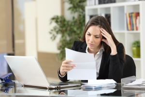 Worried businesswoman reading a notification sitting in a desktop at office