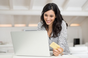 Woman on laptop with debit card