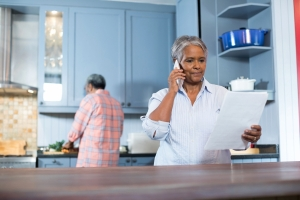 Senior woman on the phone in her kitchen reading a document