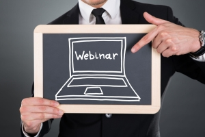 Business man holding a chalkboard with the word webinar